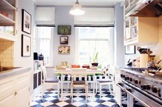 Fashion designer Kate Spade and husband Andy Spade mix geometric prints in their New York City kitchen with classic black and white floor tiles and a striped upholstered bench.