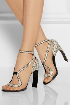 Nicholas Kirkwood:Finished with a signature curve heel, these elaphe sandals are crafted with clear acetate panels so the flowing lines seem to float over the foot. $1,295