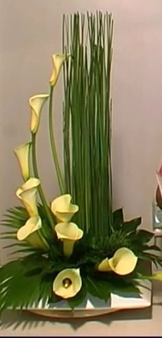 Cali Lillie's yellow. straight greenery on right side. Lillie's at base and bigger green leaves around bottom Contemporary Flower Arrangements, Tropical Floral Arrangements, Creative Flower Arrangements, Ikebana Flower Arrangement, Church Flower Arrangements, Ikebana Arrangements, Beautiful Flower Arrangements, Floral Centerpieces, Beautiful Flowers