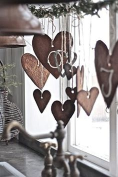Cinnamon dough hearts on string with a bit of garland along kitchen window