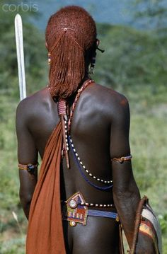 Kenya. Maasai warrior with long ochred braids tied in a pigtail. This singular hairstyle sets him apart from other members of his society. His beaded belt is of a style only worn by warriors.