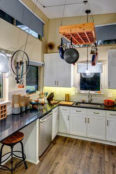 Inside the tiny house is a large kitchen with white shaker style cabinets, black silestone counters, farmhouse sink, four burner range, white subway tile backsplash, and a dishwasher.
