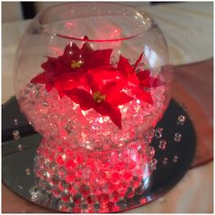 Fish bowl wedding centrepiece for Christmas themed weddings. Clear beads lit up with red lights and red Christmas flowers. Available to hire for your wedding in Swansea, Neath, port talbot, Bridgend, porthcawl, Llanelli, Carmarthen and surrounding areas of South Wales from affinity event decorators www.affinityeventdecorators.com