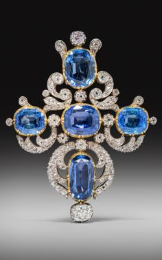 A Victorian sapphire and diamond cruciform pendant, the five oval-shaped sapphires are set in gold cut down collets and set with cushion-shaped diamonds in silver scrolls. 7.2cm high.