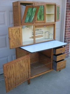 """OAK Hoosier WILSON Cabinet w Flour Bin, Slag Glass Doors, 9 pc. Glassware restored to a medium oak tone clean. GREEN SLAG GLASS, tilt out FLOUR BIN, Spice Rack with ROLLING PIN & 5 original SPICE JARS, porcelain pull out work top trimmed in black, wire POT & Pan shelf, door mount wire LID RACK, Roll Tambour Door,Wilson tag metal drawers. on casters and is a 2 pc. unit. This cabinet measures 71""""H x 41""""W x 27""""D and you can add 6"""" to the depth with the work top extended. Columbus Ohio area"""