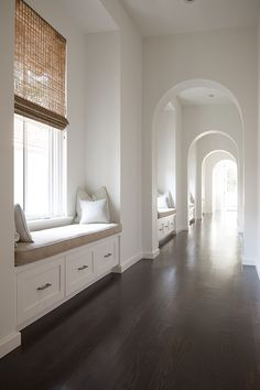 Transitional, Entrance/foyer. Stunning hallway lined with built-in window seats with storage drawers topped with beige seat cushions and gray pillows below windows dressed with woven shades separated by arched doorways over dark hardwood floors