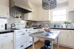 Vintage design elements were preserved in the kitchen like the hexagon countertop tile and the classic stove. To spice things up, a stainless steel backsplash and modern pendant were added.
