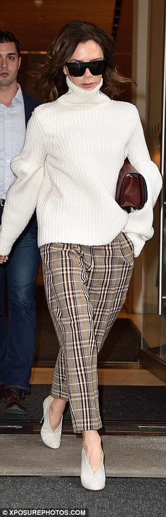 Stylish: Teaming it with wide-fit checked trousers, she accentuated her stature with a pai...
