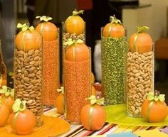 Autum centerpiece. Don't forget ot look at your local dollar store for different types of clear containers. Then use dried beans and nuts to fill and top with a small pumpkin.