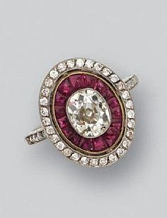 DIAMOND AND RUBY RING. Set with an oval-shaped diamond weighing approximately 1.20 carats, within a frame of calibré-cut rubies, the outer border and shoulders set with small old European-cut diamonds, mounted in platinum and gold