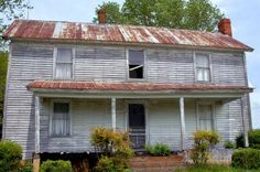 Vintage farm house has tin roof, clapboard sides, chimneys and front porch  Stock Photo