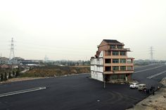 A half-demolished apartment building stands in the middle of a newly built road thanks to a Chinese couple that refused to move in Wenling, in eastern China's Zhejiang province, on <span>November 22, 2012</span>. Luo Baogen, 67, and his 65-year-old wife waged a four-year battle to receive more compensation than was offered by the local government of Daxi, a Chinese newspaper said.
