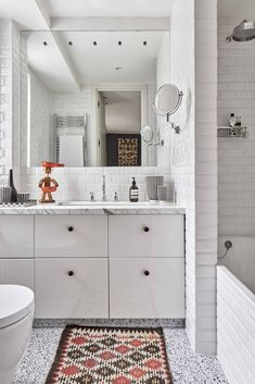 "A simple white bathroom in [link url=""http://www.houseandgarden.co.uk/gallery/christine-van-der-hurd-house""]Christine Van Der Hurd's London house[/link] is livened up with a colourful rug."