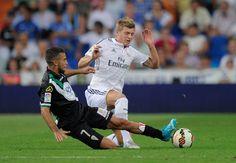 Fausto Rossi of Cordoba CF tackles Toni Kroos of Real Madrid during...