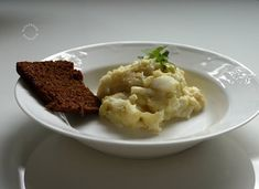 """Plokkfiskur is this awesome Icelandic traditional dish made from fish potatoes onion and bechamel sauc. So simple and delicious (though seasoned quite heavily with white pepper). The name means mashed fish and that it is essentially, combined with potatoes.  It was every time served with a very dark coloured bread that looks a bit like Danish rye bread but tastewise it's closer to Finnish """"archipelago bread"""": sweet with malted flavour, resembling mämmi in bread form (Finnish Easter dessert)."""
