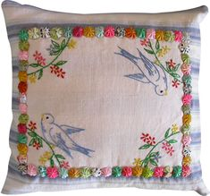 Cushion made with a vintage embroidered piece in the middle and fabric flowers added
