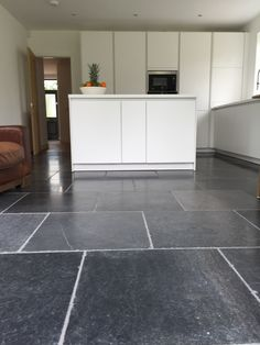 Antiqued blue stone flagstones used for kitchen flooring. These durablelimestone tiles can be used for both inside and outside projects. A colour enhancer was used to bring out the variation in the limestone. Nice alternative to Buxton stone flooring.
