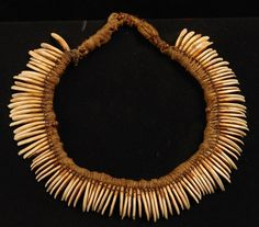 Papua New Guinea   Necklace; a tube of fabric, filled with cord material and embroidered with teeth (tree cangeroo), on wooden board coated with black velvet   150€ ~ sold