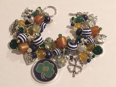 Handmade Notre Dame Charm Bracelet: Chunky Cluster Bracelet with various Navy, Gold, and Green beads and doubled sided Notre Dame Charm by RoyalStreetBoutique on Etsy