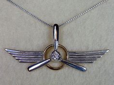 This beautiful handcrafted sterling silver 3 bladed prop in 14kt gold filled ring with sterling silver wings with a box chain necklace is a classic piece for anyone who love aviation! This necklace comes with a 4mm cubic zirconia birthstone (April). $80