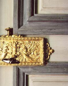 Elaborate door handle with gold embossed plate.
