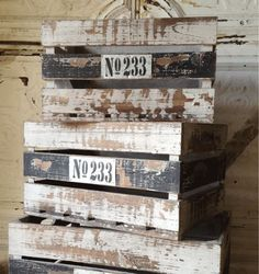 A set of three wooden crates in black and white stripes, with a stripped paint and distressed finish that gives them a rustic and salvaged look. Each crate has No.233 label on it. Available sizes: Small: 15 x 10 x 8 Medium: 17 x 11 x 9 Large: 19 x 13 x 10