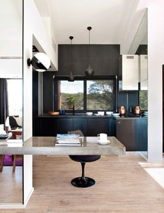 Source: Elle Deco Espana Loving so many things about this cool and contemporary kitchen! and of course, a cool kitchen must have cool designer pieces such as the Tom Dixon Beat pendant lightsand Saarinen Tulip Chairs, in black no less!