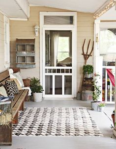 I like the plain wood bench with pillows, the rug the colored the walls with the white screen door, the rustic/farmy decor, and the plants.
