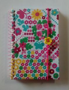 Caderno pequeno 10x15cm, capa dura, 96 folhas, forrado com tecido colorido de fundo branco e com elástico decorado para mantê-lo fechado.