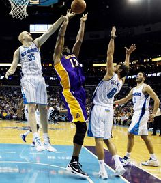 Los Angeles Lakers' center Andrew Bynum (17) shoots over New Orleans Hornets center Chris Kaman (35) and New Orleans Hornets' shooting guard Marco Belinelli (8) during the second half of their NBA basketball game in New Orleans, Louisiana April 9, 2012.