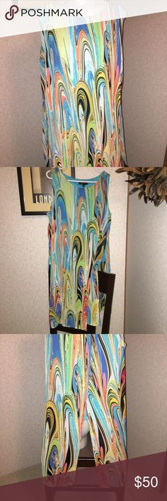 Melissa Paige XL Swirl Girl Multi Tunic S/S NWT Melissa Paige XL Exaggerated Column Tunic in Swirl Girl S/S. Covered in an Artistic Oil-Spill Pattern, this Tunic Adds a Vibrant Pop to Any Look. Accented W/A Split Back, This Elongated Top Will Take you from Day to Night in Standout Style.Aprox. 38in-L Bust-24in-W Pullover,Sleeveless,Partially Lined & 100% Poly. Melissa Paige Tops Blouses