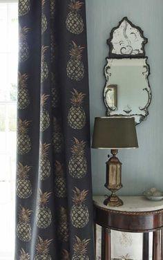 Pineapple Fabric - The pineapple is often considered a symbol of hospitality in the home. This fun contemporary linen cotton fabric features a hand block print effect pineapple design in gold and copper on a deep charcoal ground, for a moody raj-style room.
