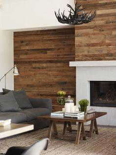 Holz Wandverkleidung und Kaminofen und graues Sofa