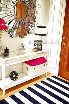 A console table is a great addition to any entry way for keys, storage and style! Contrasted beautifully with a black and white striped rug, starburst mirror and pops of hot pink.