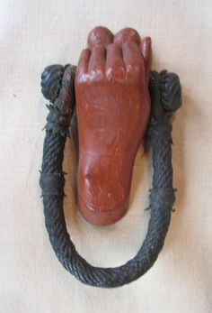 Figural becket cleat in the form of a heart in hand.