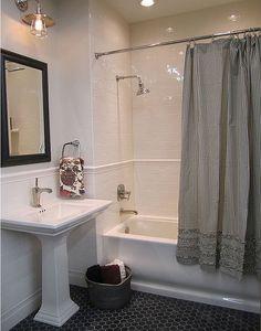White bathroom from Shelter Interior Design blog - white subway tiles, dark coin floor tiles, black and white stripe curtain