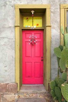 watermelon pink door and mustard yellow trim on grey stucco with cactus garden