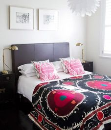 Don't love the throw pillows, but the sconces, headboard, and the bright suzani are great