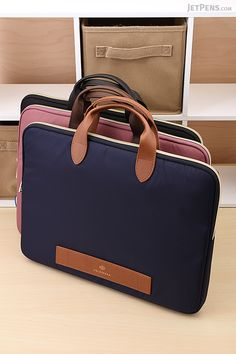 "Stylish Mark's Carrying Cases boast faux leather handles and can hold an A4 size notebook or 13"" laptop in their padded main compartments. Multiple interior pockets let you organize pens, papers, and other accessories."