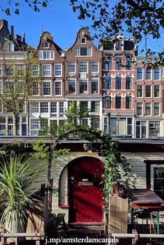 A row of 17th, 18th, and 19th century houses along Prinsengracht, a canal in the center of Amsterdam. In the front is the entrance to a houseboat.