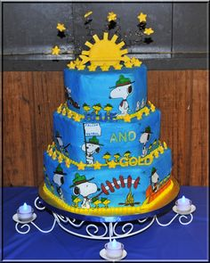 Cub Scouts Blue and Gold Cake - Cake frosted with buttercream, then food color sprayed blue. I used the frosting sheets and drew Snoopy and Woodstock with edible food markers. Cut them out and adhere'd to the cake. Stars and Arrow of Light topper are made from candy melts.
