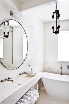 white bathroom, oversized circle mirror, lighing fixture, open shelves, stone sink.