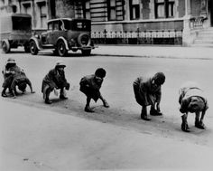Children playing leap frog in a Harlem street, ca. 1930.