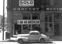 """This store owned by a man of Japanese ancestry is closed following evacuation orders in Oakland, California, in April of 1942. After the attack on Pearl Harbor the owner had placed the """"I Am An American"""" sign in the store front window."""