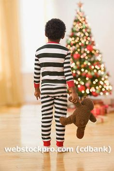 African boy in pajamas with teddy bear looking at Christmas tree - Royalty Free Stock Photo