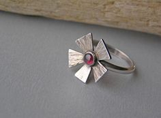 Flower Design Sterling Silver Ring with Garnet. All metal parts of this ring were hand cut from silver, textured, soldered. The ring has a floral design - shaped as a flower and a garnet cabochon is set in the center of the flower. The ring was slightly oxidized and polished. Size 6.5 (16.9). The flower is about 0.6x0.6 (1.5cm x 1.5cm). The band is about 2.2 mm width.  Ring will be packed in a small gift box.