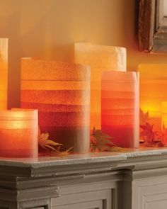 Hurricane vases are wrapped in layers of colored tissue paper for a glowing effect.