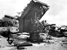 This is one of the ten 10.5cm guns salvaged from the wreck of the SMS Königsberg and used in the land campaign in German East Africa during the First World War. 10.5cm SMS Königsberg Gun as it was Captured at Mwanza, Tanzania, July 1916. It is mounted on its original fixed pivot stand with a wooden shield camouflaged with branches and leaves. Its recoil springs have been removed and lie on the ground. The breech block has also been removed. Photo © Lt Col CG Hill Collection, Imperial War…