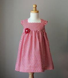 The Maisie Dress! This lovely red chevron dress has an empire waist with a lined bodice. Sweet little ruffles at the shoulder give the Maisie dress a slight cap sleeve. There is a removable red and white polka dot flower pin at the waist for an extra pop of fun! It has a single button closure at the back.