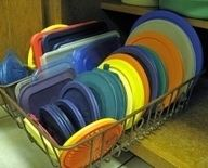 Use a dish drainer to organize pot lids, or Tupperware lids in a cabinet. You can find them in all sizes now, to fit almost any cabinet, and they are super cheap at the dollar store!